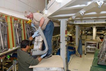 Instalacja paneli RCC na krawędzi natarcia lewego skrzydła wahadłowca Atlantis.  To właśnie uszkodzenie jednego z takich paneli było przyczyną katastrofy STS-107. Credits: NASA