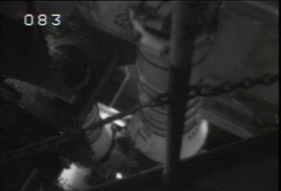 Dolny segment prawej rakiety SRB (aft segment) jest opuszczany na MLP-2 celem przymocowania za pomocą czterech sworzni mocujących.  Analogiczny lewy fragment jest widoczny w tle (NASA)