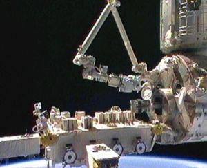 Główny japoński manipulator wyciąga ramię SFA ze śluzy, po środku widoczna paleta z eksperymentami EF / Credits: spacefellowship.com