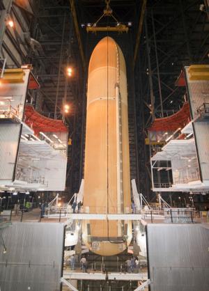 Zbiornik ET-136 opuszczany na platformę, u dołu widoczni ludzie / Credits: NASA-KSC