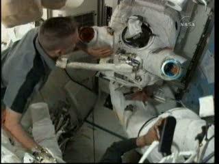 Astronauta Reisman (pod skafandrem kosmicznym - inni astronauci mu pomagają się rozebrać) / Credits - NASA TV