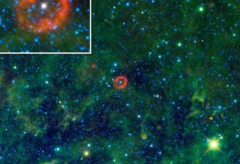 Obraz kompozytowy przedstawiający gwiazdę V385 Carinae wraz z otaczającą ją chmurą materiału. W trakcie składania załączonego obrazu, poszczególne długości fal podczerwonych, rejestrowanych przez detektor WISE, zostały oznaczone różnymi kolorami - czerwonym dla 22 mikronów, zielonym dla 12 mikronów oraz niebieskim dla 3.4 oraz 4.5 mikrona. Zielone obłoki są relatywnie ciepłym pyłem, podczas gdy niebieskie kropki stanowią gwiazdy w naszej galaktyce. (NASA/JPL-Caltech/UCLA)