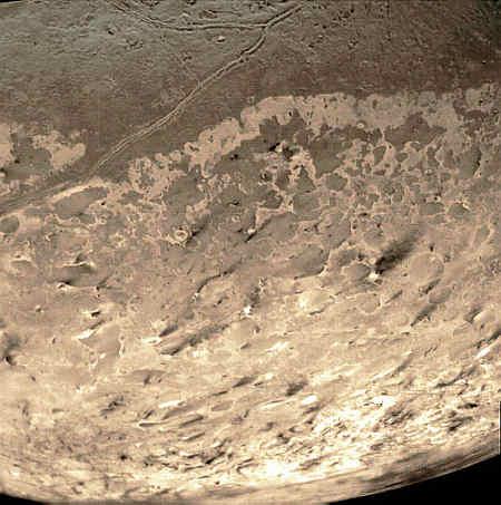 Powierzchnia Trytona, na której widoczne są ciemne ślady składająće się z węglowodorów (NASA/Ilmari Karonen)