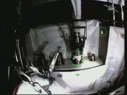 Wyciek amoniaku ze złącza M3; zielonym kólkiem zaznaczono biały wyciek pod elementem QD oraz unoszący się płatek, który oderwał się od złącza (NASA TV)
