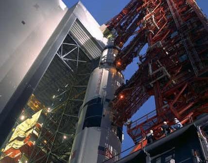 Czerwona wieża LUT zamontowana na transporterze przytrzymuje rakietę Saturn V, która właśnie opuszcza budynek VAB (NASA/69PC-0529)