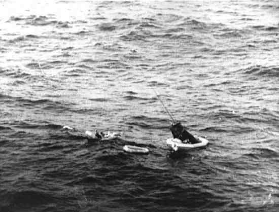 Kapsuła 'Aurora 7' po wodowaniu na Atlantyku, nurek pomaga Carpenterowi dostać się na nadmuchiwany ponton (NASA/S62-04065)