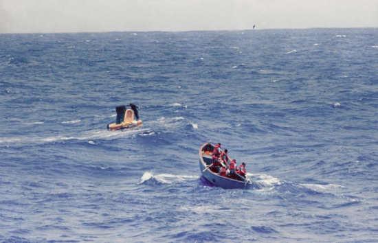 Kapsuła 'Faith 7' na powierzchni Pacyfiku; załoga wysłana z lotniskowca USS Kearsarge udaje sie do pojazdu (NASA/S63-07717)