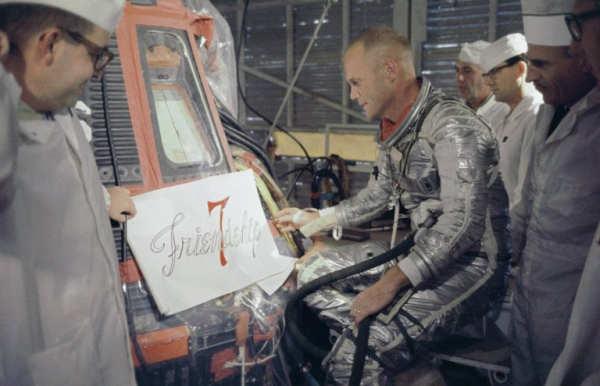John Glenn wraz z technikami ogląda wzór nazwy pojazdu Merkury, który zostanie naniesiony na kapsułę (NASA/S64-14854)