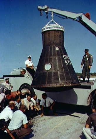 Personel Departamentu Obrony oraz technicy z firmy MacDonnell Aircraft dokonują oględzin kapsuły po jej powrocie na Przylądek Canaveral (NASA/135740)