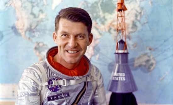 Astronauta Wally Schirra pozuje do zdjęcia w swoim skafandrze Navy Mk IV; w tle widoczna kapsuła Mercury (NASA/S62-05526)