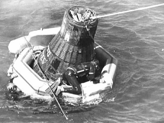 Płetwonurek Marynarki sprawdza stan kapsuły i stan mocowania liny holowniczej (NASA/S62-06160)