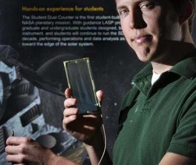 Andrew Poppe, członek zespołu studenckiego, który zaprojektował i przetestował instrument SDC, trzyma w ręku płytkę detektora (Glenn Asakawa/University of Colorado)