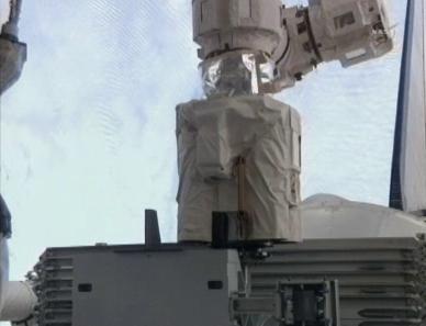 Ramię Stacji zbliża się do punktu mocowania na palecie ELC (NASA TV)