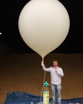 Jeden z organizatorów prezentuje balon który wyniósł do stratosfery papierowe samoloty (Credits:projectspaceplanes.com)