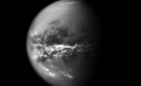 Ilustracja przedstawia metanowe chmury okalające równik Tytana (jasne obszary). [Image credit: NASA/JPL/SSI]
