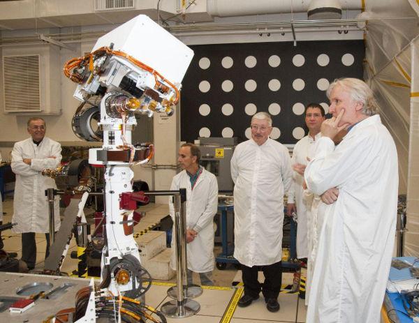 Grupa inżynierów oraz James Cameron obserwują działanie modelu inżynieryjnego masztu z kamerami łazika MSL (NASA/JPL)