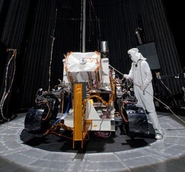 Na zdjęciu testowanie łazika Mars Science Laboratory w mierzącej 7,6 metrów średnicy komorze ciśnieniowej. Łazik był w tym momencie wyposażony w cały podstawowy sprzęt oraz instrumenty. Po zamknięciu włazów komory, możliwe jest uzyskanie warunków bliskich próżni. Dzięki przepompowywaniu ciekłego azotu przez ściany komory, możliwe jest uzyskanie temperatury -130 stopni Celsjusza. Potężne lampy pod sufitem komory są w stanie symulować promieniowanie słoneczne obecne na Marsie. Technik, widoczny na zdjęciu, korzysta ze specjalnego przyrządu w celu ustalenia intensyfikacji symulowanego promieniowania słonecznego w różnych rejonach komory / Credits: NASA/JPL-Caltech