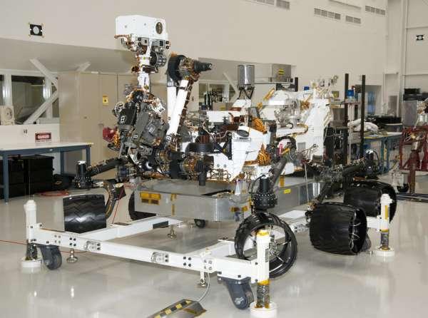 Podgląd na łazik z lewego przedniego rogu maszyny, spoczywającej na wózku sprzętowym. W momencie gdy koła Curiosity są na ziemi, to szczyt masztu znajduje się na wysokości 2,2 metra / Credits: NASA/JPL-Caltech