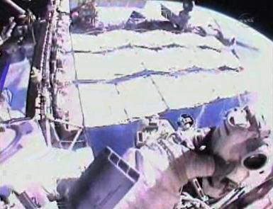 Widok z kamery zainstalowanej na hełmie Chamitoffa, w prawym dolnym rogu widoczny aparat fotograficzny (NASA TV)