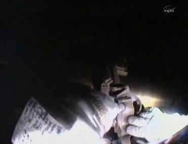 Chamitoff poprawia mocowanie na platformie narzędziowej, widok z kamery hełmu (NASA TV)