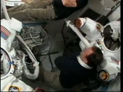 Podgląd na wnętrze przedziału sprzętowego modułu Quest, w którym trwają przygotowania do spaceru kosmicznego. W tle widoczne skafandry EMU, w które niebawem ubierani będą Fincke i Chamitoff / Credits: NASA TV