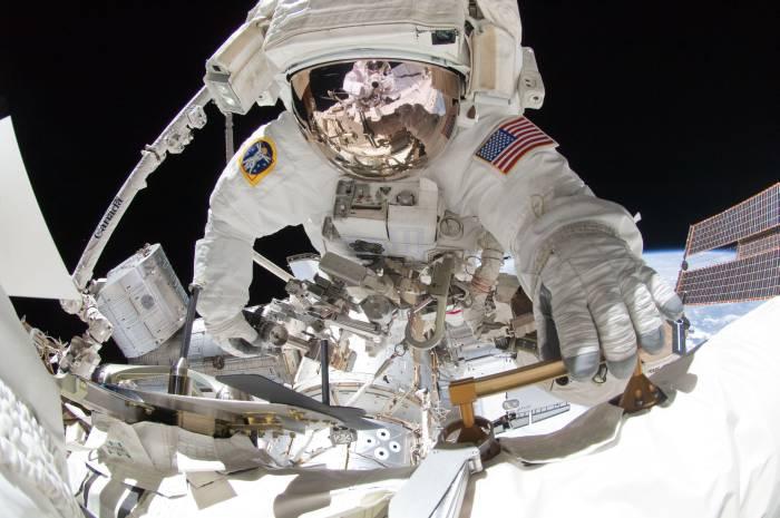 Astronauta Greg Chamitoff, w odbiciu jego hełmu widać fotografa - Mike'a Fincke / Credits: NASA