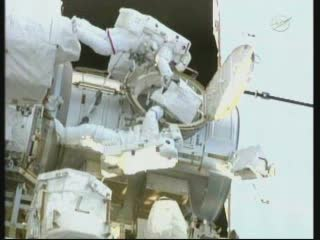 Godzina 08:27 CEST - astronauci w przestrzeni kosmicznej, obok śluzy Quest. / Credits - NASA TV