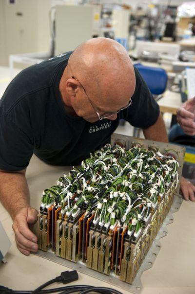 Technik po zdjęciu osłony ALCA-2 przygląda się wewnętrznej aparaturze / Credits: NASA/Kim Shiflett