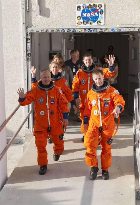 Astronauci misji STS-135 opuszczają budynek Operations and Checkout Building, w którym są przygotowywani (np. ubierani w charakterystyczne pomarańczowe ciśnieniowe skafandry ACES), i wsiadają do czekającego Astrovana, mającego przewieźć ich na stanowisko startowe / Credits: NASA/Kim Shiflett