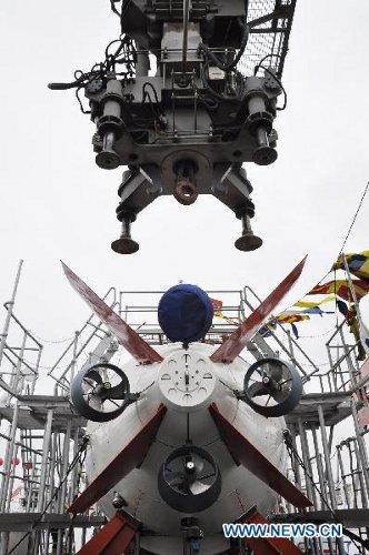 Zdjęcie wykonano 1 lipca 2011 roku. Przedstawia podwodny okręt Jiaolong, ładowany na Xiangyanghong 09, naukowy statek badawczy. Załadunku dokonano w porcie miasta Jiangyin, w prowincji Jiangsu, we wschodniej części Chin. Jiaolong rozpoczyna swoją podróż, w trakcie której zanurzy się na głębokość 5000 metrów, kontynuując zeszłoroczne testy, w trakcie których osiągnął granicę 3579 metrów. [Credits: Xinhua]