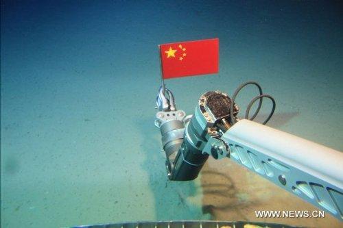 Automatyczne ramię podwodnej, załogowej łodzi Jiaolong, utwierdza na morskim dnie flagę Chińskiej Republiki Ludowej, w trakcie testów głębinowych w lipcu 2010 roku. Osięgnięto wtedy 3579 metrów zanurzenia, co dało ChRL miejsce w piątce krajów, których załogowe łodzie podwodne przekroczyły granicę 3500 metrów – Stanów Zjednoczonych, Rosji, Francji i Japonii. [Credits: Xinhua]