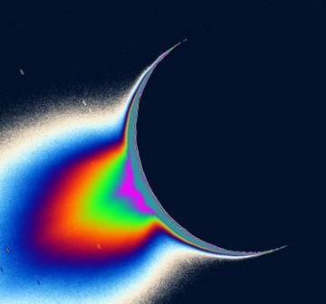 Ilustracja ukazuje fontanny wyrzucanych z Enceladusa cząstek. Wydobywają się one z bieguna południowego księżyca, z okolic tygrysich pasów. Obróbka i nałożenie fałszywych barw, wyraźnie uwidaczniają nienormalnie powiększony obszar wyrzutu najlżejszych cząstek (najjaśniejszy). [Credits: NASA/JPL/Space Science Institute]