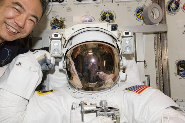 Satoshi Furukawa oraz Ron Garan w czasie testów procedur rozpoczęcia spaceru kosmicznego. W odbiciu hełmu Garana widoczny jest Mike Fossum / Credits: NASA