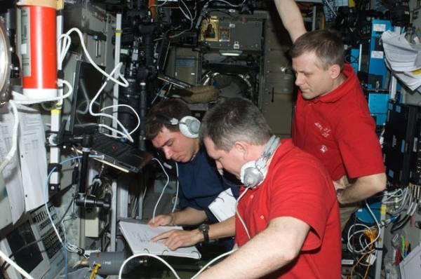 Kosmonauci Wołkow (po lewej), Samokutiajew oraz Borisienko (po prawej) monitorujący dane podczas automatycznego dokowania statku transportowego Progress 43P. W każdej chwili byli oni gotowi do przejęcia manualnej kontroli nad statkiem za pomocą systemu TORU / Credits: NASA