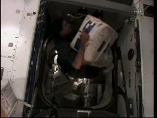 Osoba z załogi dokonująca transferu ładunku z modułu Rafaello / Credits: NASA TV