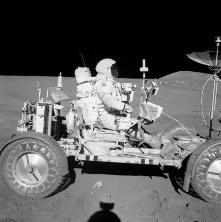 David Scott podczas testowych przejazdów podczas EVA-2. W oddali widać rozstawioną poprzedniego dnia stację ALSEP. Na pojeździe LRV widoczne są: mapa obszaru badań, kamery, a także Buddy Secondary Life Support System (BSLSS), który zawieszony jest za fotelem astronauty. BSLSS zawiera system węży, które umożliwiają współdzielenie zasobów wody i tlenu przez astronautów. (NASA)