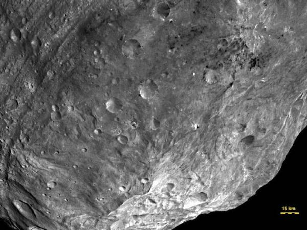 Zdjęcie ukazujące rejon bieguna południowego, niesamowicie chaotycznie ukształtowaną powierzchnię Westy, gdzie widoczne jest centralne wzniesienie oraz gigantyczne, podobne do zmarszczek bruzdy, które rozciągają się wzdłuż równika planetoidy. Niewidoczne na tym zdjęciu tereny na północ od tych bruzd są z kolei mocno poznaczone kraterami / Credits: NASA