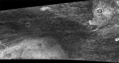 Radarowe zdjęcie powierzchni Tytana pozyskane 21 czerwca 2011 roku przez sondę Cassini. Jasny obszar w lewym dolnym rogu to twór powierzchniowy wielkości kontynentu - Xanadu. Faliste pasy powyżej to wydmy, podobne do tych z ziemskich pustyń. W prawym górnym rogu znajduje się krater Ksa. Credits: NASA/JPL