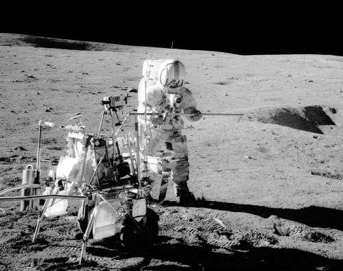 Alan Shepard pracujący na powierzchni Księżyca, po lewej dwukołowy wózek na próbki i narzędzia - MET (NASA)
