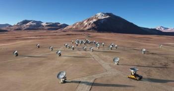 Wizja artystyczna ukończonego kompleksu ALMA, składającego się domyślnie z 66 radioteleskopów. Warto zauważyć, iż poszczególne anteny będzie można rozmieszczać wedle potrzeby (widoczny na grafice transporter z przenoszonym urządzeniem), zmieniając tym samym rozdzielczość układu / Credits: ALMA (ESO/NAOJ/NRAO)/L. Calçada (ESO)