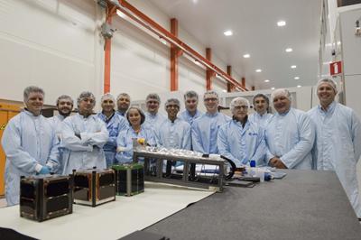 Pierwsze trzy cubesaty zamontowane na P-POD i studenci przy nich pracujących / Credits: ESA