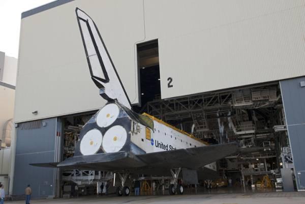 Wahadłowiec Atlantis wytaczany z hangaru OPF-2 (w dniu 20.01.2012), celem wpuszczenia drugiego orbitera - Endeavour, który przygotowywany jest do transportu na zachodnie wybrzeże USA. Na zdjęciu doskonale widoczny brak trzech głównych silników SSME oraz gondol systemu OMS / Credits: NASA/Charisse Nahser