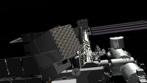Artystyczna wizja instrumentu NICER na Międzynarodowej Stacji Kosmicznej. NICER jest prostopadłościanem z okrągłymi otworami na jednej ścianie. Jest to 56 teleskopów skupiających natężenie promieniowania X z odległych pulsarów na detektorze. Credits: NASA