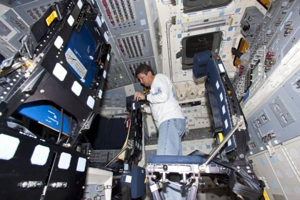 Reinstalacja siedzeń w kabinie promu Discovery / Credits: NASA/Jim Grossmann