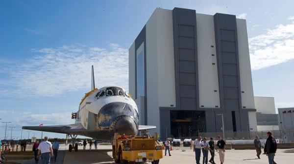 Moment transportu wahadłowca Endeavour z hali montażowej VAB (w tle) do hangaru OPF-2 / Credits: Kim Shiflett