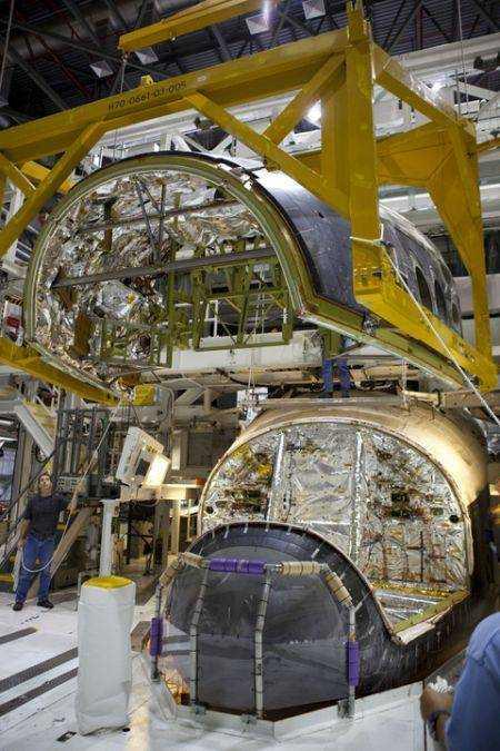 Moment zakładania z powrotem przedniej sekcji systemu manewrowego FRCS, która wysłana została razem z innymi komponentami do bazy White Sands Test Facility (Nowy Meksyk, USA), gdzie została oczyszczona z resztek toksycznych płynów (paliwa) / Credits: NASA/Dimitri Gerondidakis
