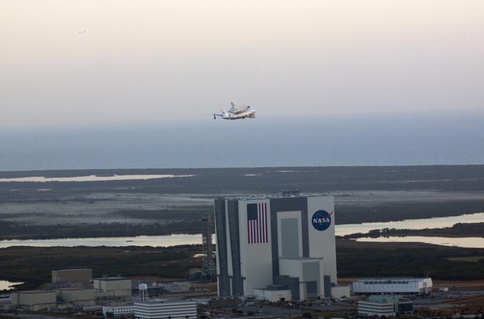 Discovery podczas pożegnalnych przelotów nad KSC (na zdjęciu budynek VAB) / Credits: NASA/Glenn Benson