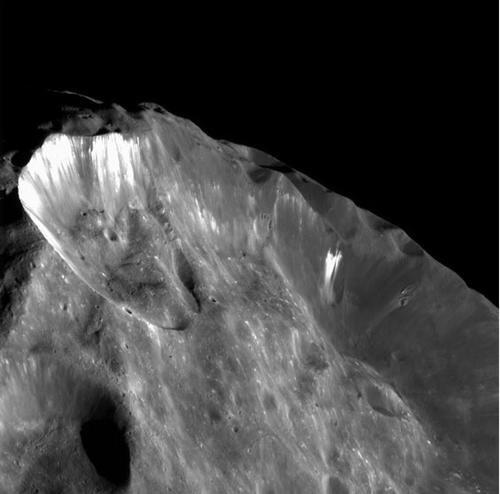 Zbliżenie na powierzchnię Phoebe - zdjęcie z 2004 roku. Pod ciemną warstwą powierzchniowego materiału znajduje się jaśniejszy lód / Credits - NASA, ESA