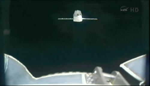 Podgląd na statek Dragon z kamery umieszczonej na końcu manipulatora SSRMS / Credits: NASA TV