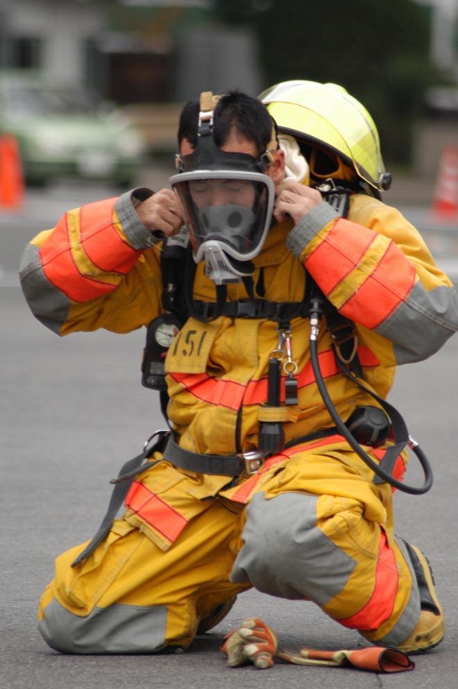 Strażak demonstruje strój bojowy. Wiele elementów jego wyposażenia, jak maska tlenowa, butla, uprzęże, zostały wykonane za pomocą technologii użytych po raz pierwszy w załogowych lotach kosmicznych.